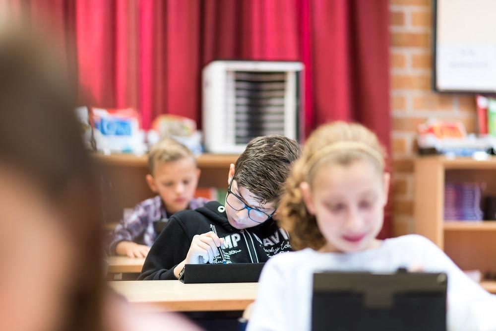 enfant utilise une tablette en classe